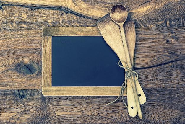 Retro-küchengeräte und vintage-tafel auf holzhintergrund. getöntes bild im vintage-stil