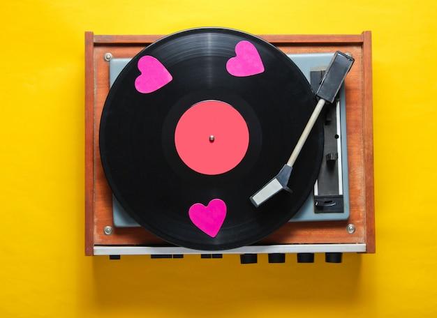 Retro-kultur. dekorative herzen auf einer schallplattenplatte auf gelbem hintergrund.