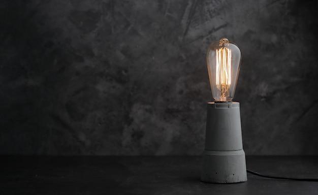 Retro lampe mit edison lampe auf beton. das konzept ist eine gute idee.