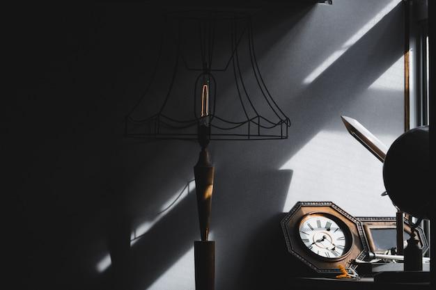 Retro- lampe, uhr und material im wohnzimmer gegen sonnenlicht und schatten vom fenster