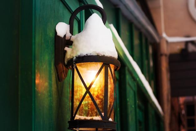 Retro laterne mit schnee bedeckt mit strahlendem licht und bokeh