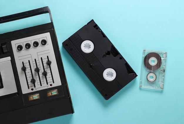 Retro-medien auf einem blau. alter audiokassettenspieler, video- und audiokassetten