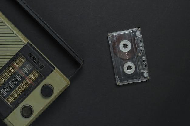 Retro-medien. radioempfänger, audiokassette auf schwarzem hintergrund. draufsicht.