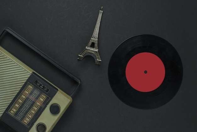 Retro-medien. radioempfänger, schallplatte, statuette des eiffelturms auf schwarzem hintergrund. draufsicht.