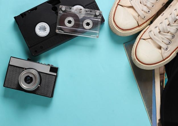 Retro-medien und zubehör auf einem blau. turnschuhe, audio- und videokassetten, kamera auf blau