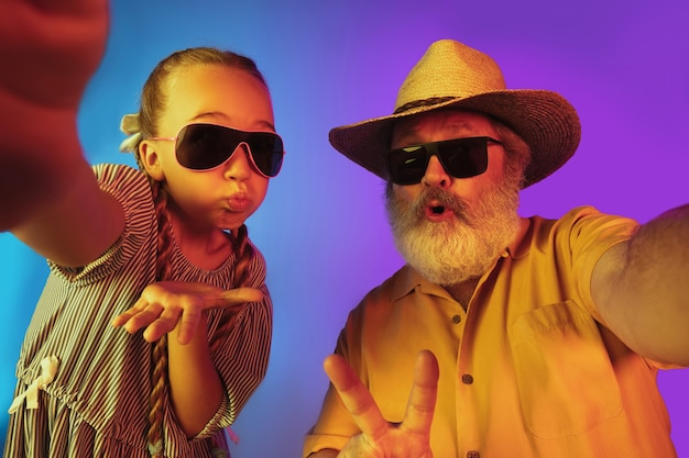 Retro-mode ist zurück. älterer mann verbringt glückliche zeit mit enkelin im neon. fröhlicher älterer lebensstil, familie, kindheit, technologiekonzept. mit altmodischem hut und sonnenbrille. exemplar.