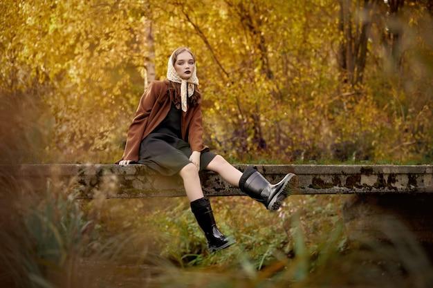 Retro-modefrau in den stiefeln, die auf einer brücke sitzen