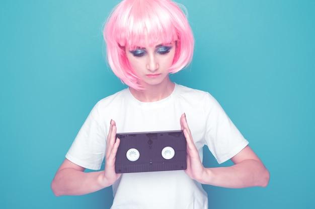Retro-modekonzept. frau mit rosa haaren hält filmhalter isoliert in einem hellblauen studio.
