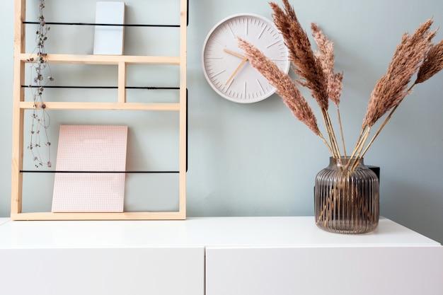 Retro moderne dekorationswand im wohnzimmer mit pastellfarben, weißer uhr und regal, moderne vase mit skandinavischem interieur aus pampagras