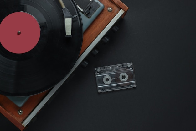 Retro musikkonzept. schallplattenspieler mit schallplatte, audiokassette auf schwarzem hintergrund. 80er jahre. draufsicht
