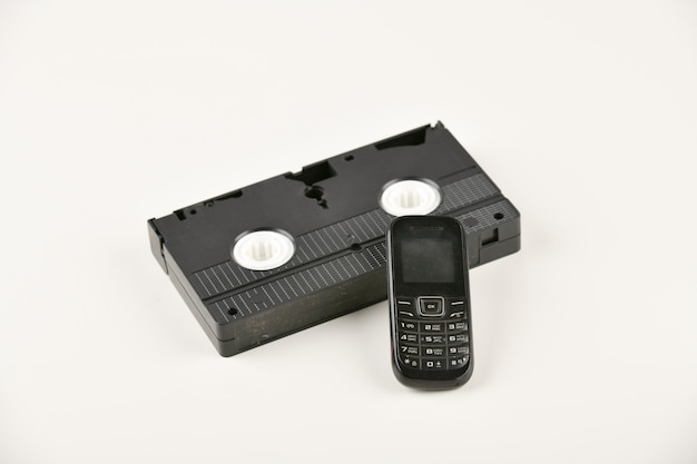 Retro objekte auf einem weißen hintergrund. telefon und videokassette mit druckknopf. analoge medientechnologie der vergangenheit. speicherplatz kopieren