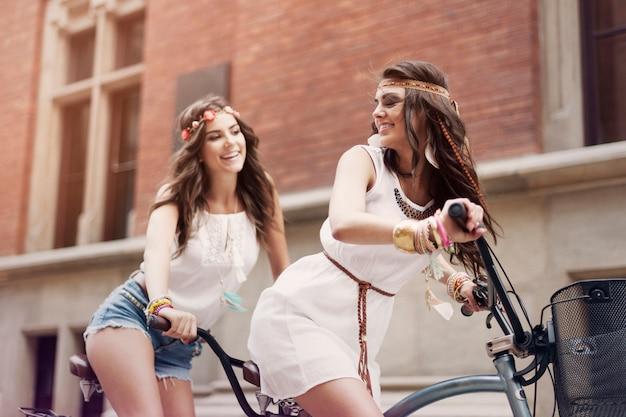 Retro-porträt von zwei freunden, die tandemfahrrad reiten