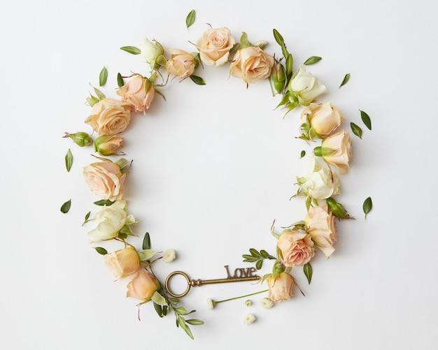 Retro-rahmen mit rosen und einem schlüssel, der auf weiß mit copyspace isoliert wird, flache lage