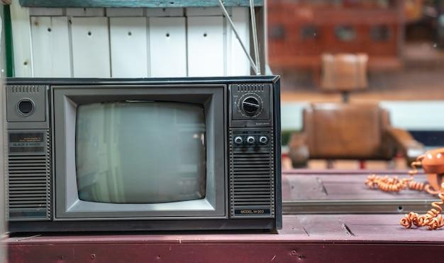 Retro- schwarzweiss-farbfernsehen der weinlese auf holztisch
