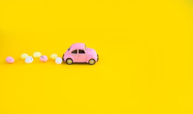Retro spielzeug rosa auto mit osterei auf dem dach. osterkarte mit platz für text auf gelbem grund.