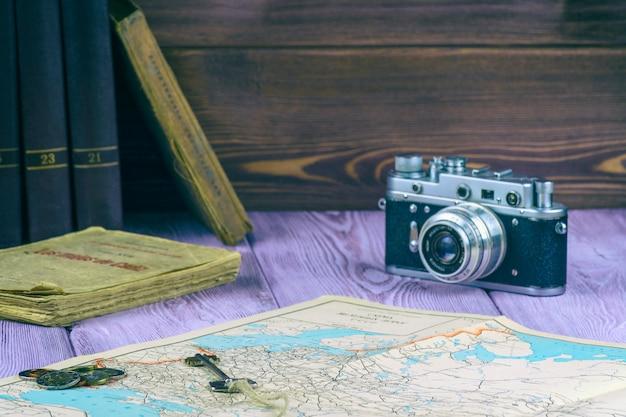 Retro-stil. alte bücher und eine karte auf dem tisch. filmkamera und eine handvoll münzen.