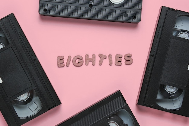 Retro-stil-konzept, 80er jahre. videokassetten auf rosa pastell mit dem wort achtziger aus holzbuchstaben