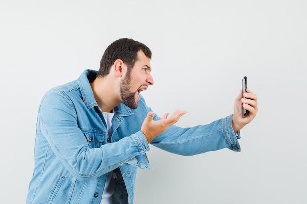 Retro-stil mann, der hand auf aggressive weise hebt, während videoanruf in jacke, t-shirt und nervös aussehen.