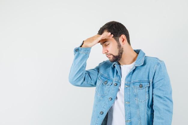 Retro-stil mann in jacke, t-shirt hand auf dem kopf halten und müde aussehen. freier speicherplatz für ihren text