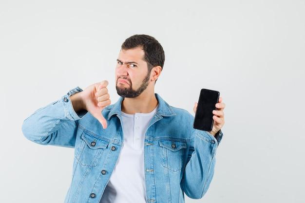 Retro-stil mann in jacke, t-shirt zeigt daumen nach unten, während telefon zeigt und unzufrieden aussieht, vorderansicht.
