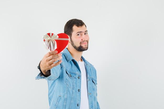 Retro-stil mann zeigt geschenkbox in jacke, t-shirt, vorderansicht.