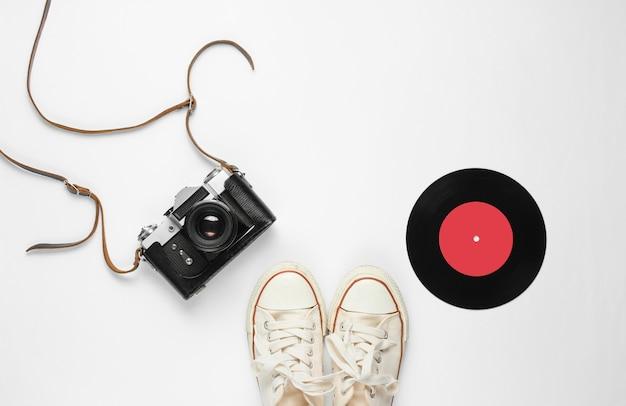 Retro stillleben. altmodische turnschuhe, schallplatte und vintage-filmkamera auf weiß. draufsicht. flach liegen