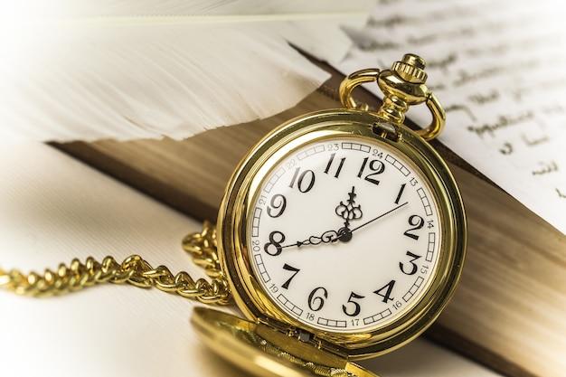 Retro-stillleben mit goldener vintage-taschenuhr, buch und handgeschriebenem brief
