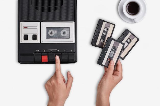 Retro-tonbandgerät, kassetten und eine tasse heißen kaffees, die auf weißer oberfläche stehen.