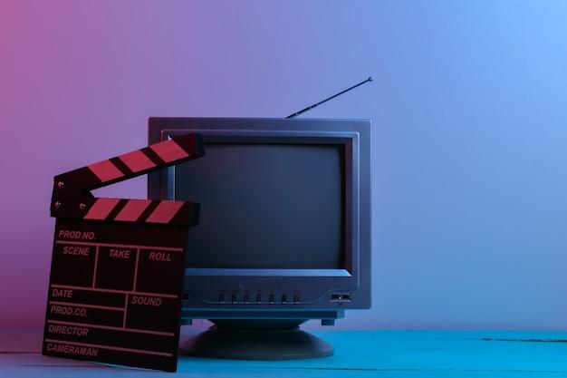 Retro-tv-empfänger mit filmklappe in rot-blauem neonlicht. unterhaltungsindustrie