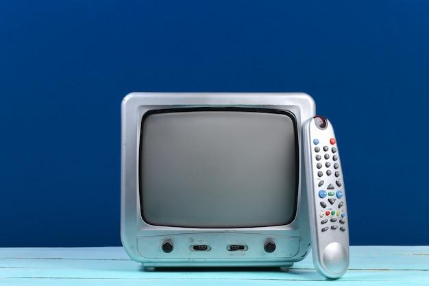 Retro-tv-empfänger mit tv-fernbedienung auf klassischem blau