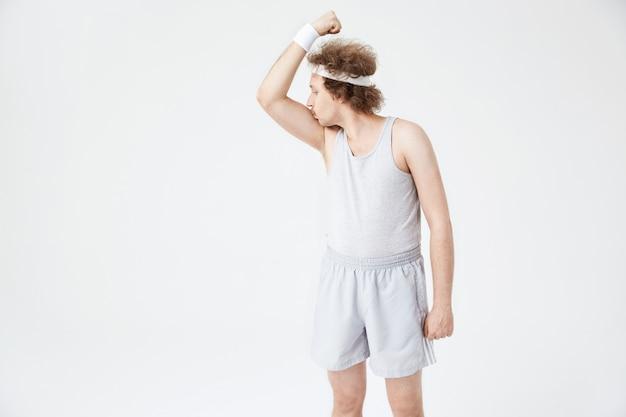 Retro-typ mit weißem stirnband, der rechten armbizeps küsst