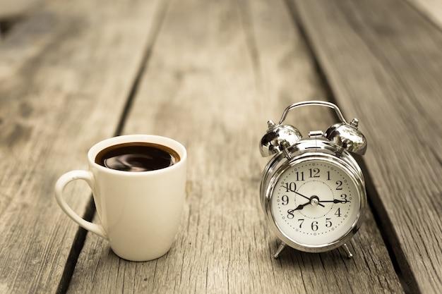 Retro uhr mit tasse kaffee