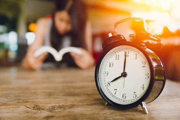Retro uhrglocke der uhr mit leuten las einen buchhintergrund. tägliches konzept lesen.