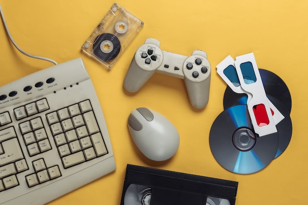 Retro-unterhaltung. altmodische tastatur, pc-maus, cds, gamepad, anaglyphenbrille, audio- und videokassette auf gelb
