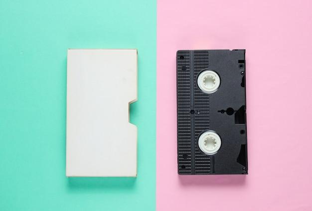 Retro-videokassette mit abdeckung auf farbiger papieroberfläche.