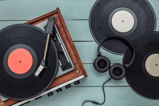 Retro-vinyl-player und stereo-kopfhörer auf blauem hintergrund aus holz. ansicht von oben. flach legen