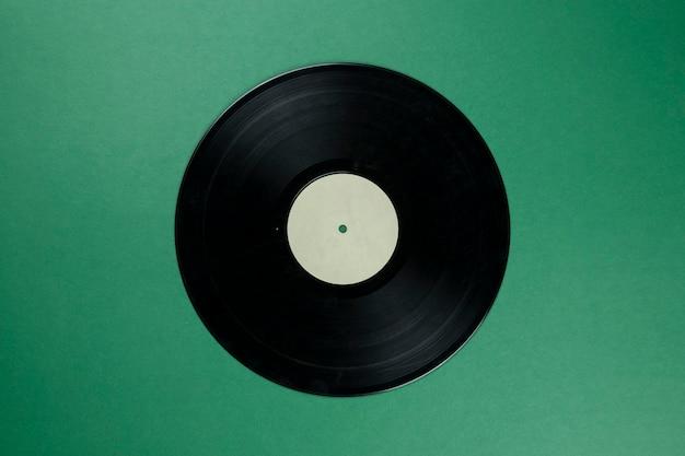 Retro vinyl-schallplatte mit leeren weißen etikett auf grün