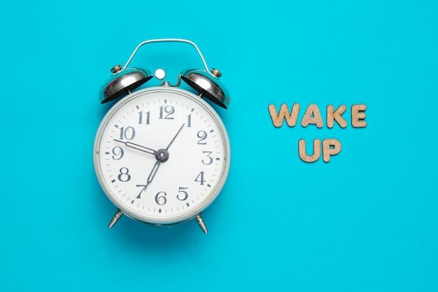 Retro wecker auf blauer oberfläche mit text wachen mit buchstaben auf minimalistisches konzept