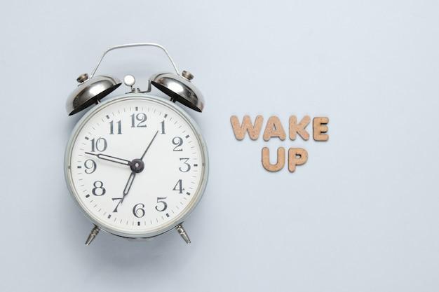 Retro wecker auf grauer oberfläche mit text wachen mit buchstaben auf minimalistisches konzept