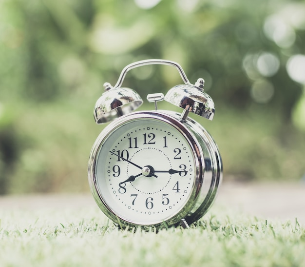 Retro wecker auf grünem gras