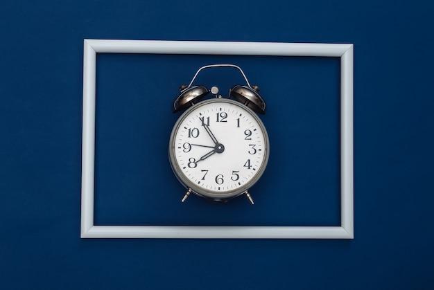 Retro-wecker auf klassischem blauem hintergrund mit weißem rahmen. farbe 2020. ansicht von oben