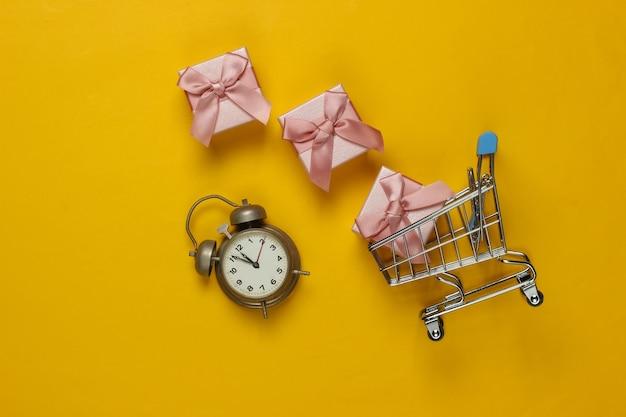 Retro wecker, einkaufswagen, geschenkboxen mit schleife auf gelbem hintergrund. 11:55 uhr. neujahr, weihnachtskonzept. urlaubseinkauf. draufsicht