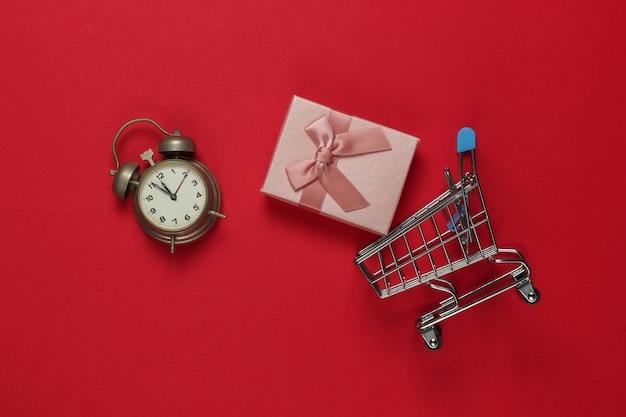 Retro wecker, einkaufswagen, geschenkboxen mit schleife auf rotem hintergrund. 11:55 uhr. neujahr, weihnachtskonzept. urlaubseinkauf. draufsicht