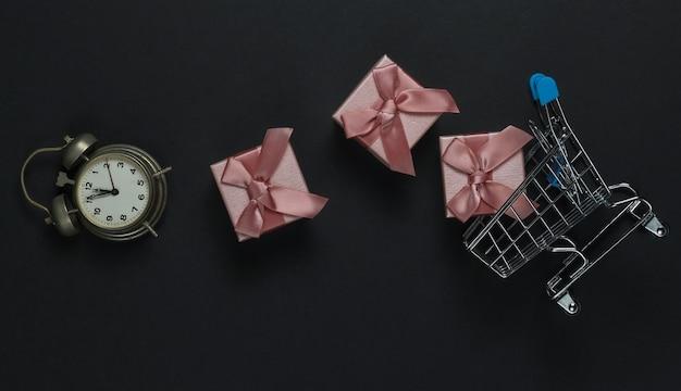 Retro wecker, einkaufswagen, geschenkboxen mit schleife auf schwarzem hintergrund. 11:55 uhr. neujahr, weihnachtskonzept. urlaubseinkauf. draufsicht