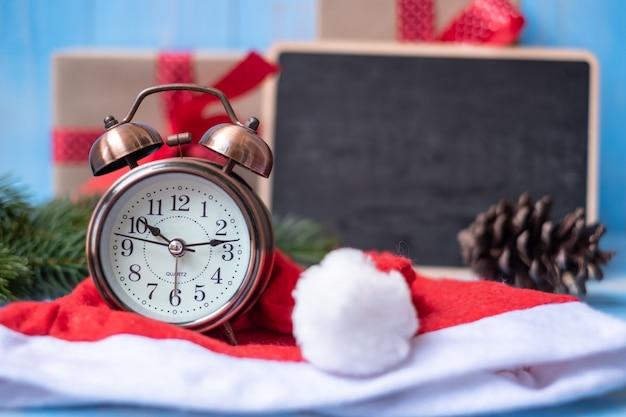 Retro wecker mit geschenkbox der frohen weihnachten oder geschenk und weihnachtsmann-hut