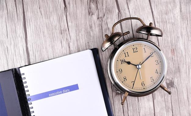 Retro-wecker mit notizbuchpapier auf dem tisch