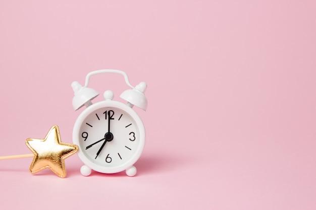Retro- wecker mit parteidekoration auf rosa hintergrund
