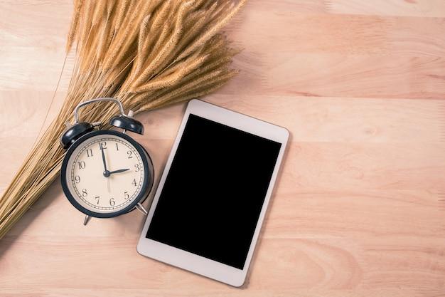 Retro- wecker und intelligentes telefon der digitalen tablette auf holz