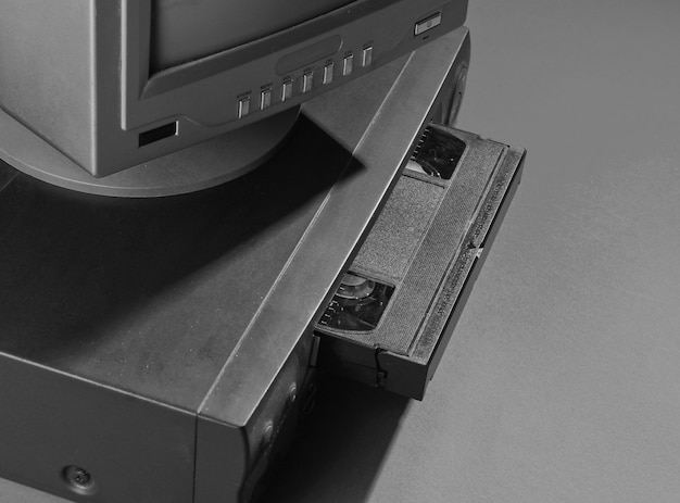 Retro welle, minimalismus 80er konzept. videoplayer mit vhs-kassette, altem fernseher, neonlicht.