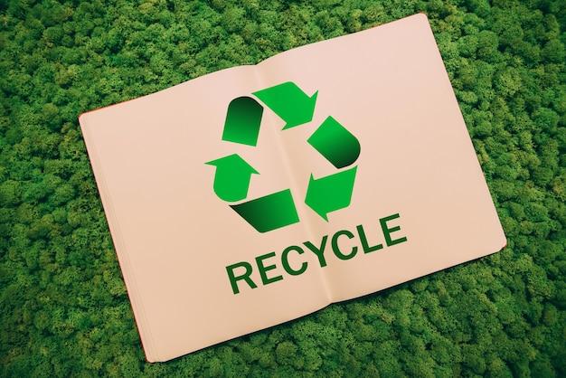 Rette den planeten. nahaufnahme des notebooks mit recyclingsymbol und text auf mooshintergrund